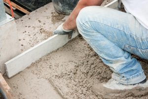 A worker laying concrete