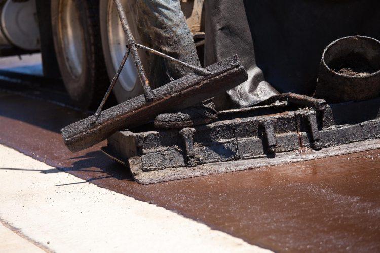 A worker and vehicle providing asphalt sealcoating