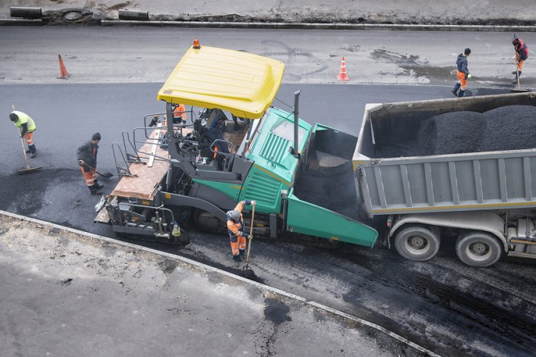 a large truck and workers laying asphalt
