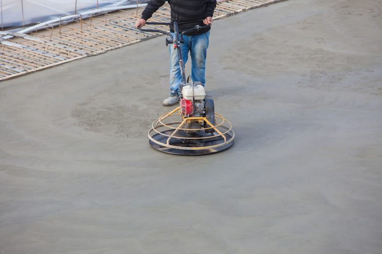 A worker smoothing concrete